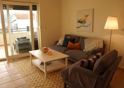 WH 1:2 Allrum med soffa och TV, utgång till balkongen.